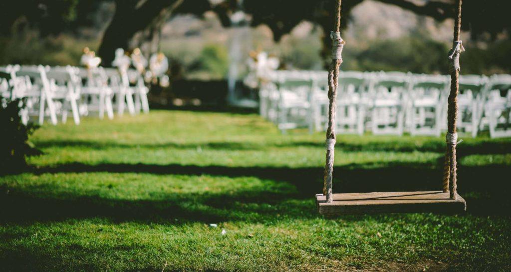 Empty outdoor garden wedding ceremony with swing seat